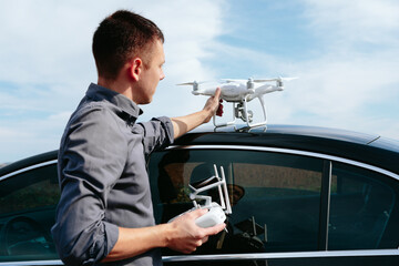 Wall Mural - A man standing near the car launches a drone. drone flight in yellow field
