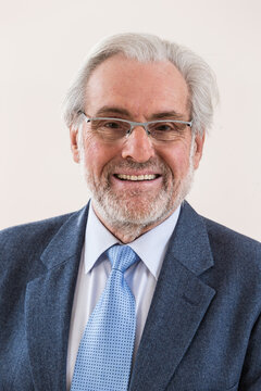 Studio shot of happy senior bearded man smiling with eyeglasses against white background