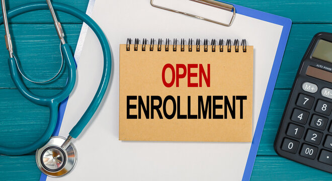 Notepad with text OPEN ENROLLMENT, calculator and stethoscope.