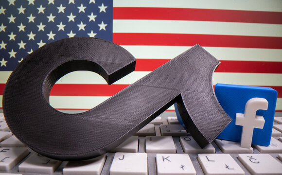 A 3D printed Tik Tok and Facebook logo are placed on a keyboard in front of U.S. flag in this illustration