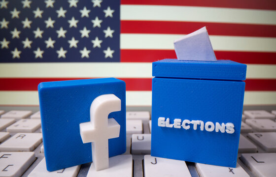 A 3D printed elections box and Facebook logo are placed on a keyboard in front of U.S. flag in this illustration
