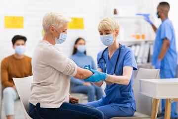 Photo sur Plexiglas Dinosaurs Senior Patient Lady Getting Vaccinated Against Coronavirus Sitting In Hospital