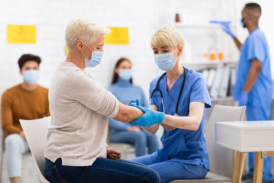 Senior Patient Lady Getting Vaccinated Against Coronavirus Sitting In Hospital