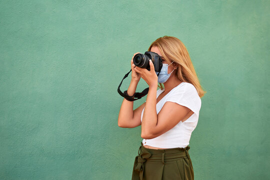 Young woman with a mask and a camera on a green background