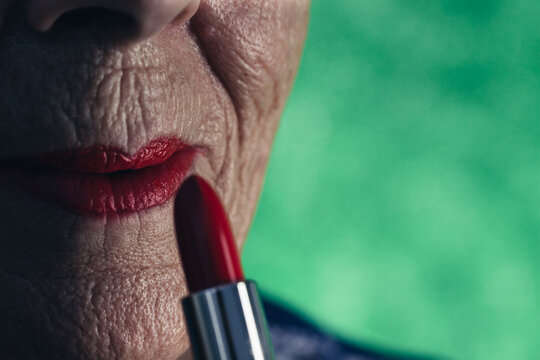 Elderly woman with lipstick and red painted lips in green background