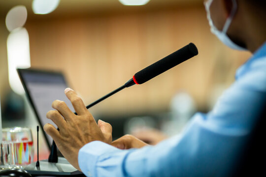 Selective focus to desktop wireless conference microphones with blurry businessman wearing mask in a meeting room, microphone on the desk in meeting room with blurry speaker. The concept of speaking.
