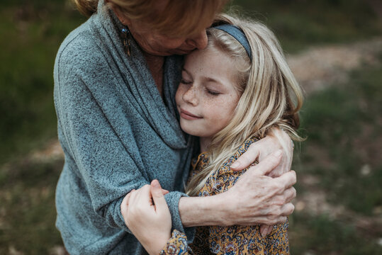 Close up of grandmother embracing granddaughter while standing in forest