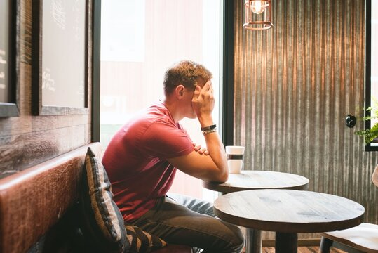 man sat covering his face looking stressed whilst in a cafe drinking