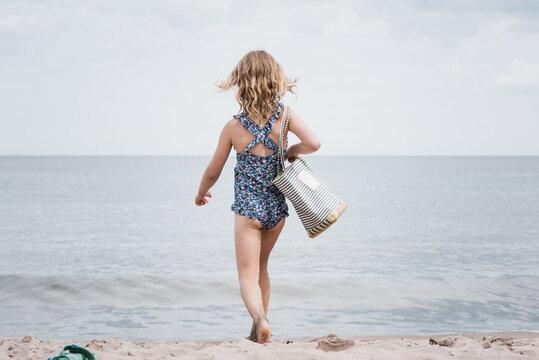 young girl holding a beach bag strutting towards the sea