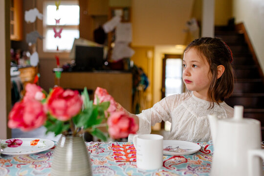 A small child in a lace dress sits alone at a table set for tea party