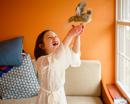 A child laughs with delight holding a flapping bird aloft in her hands