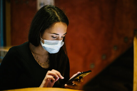 Woman wearing a mask using a mobile phone in a restaurant