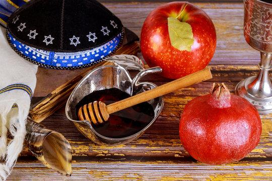 Shofar and tallit with glass honey jar and fresh ripe apples. Jewesh new year symbols. Rosh hashanah