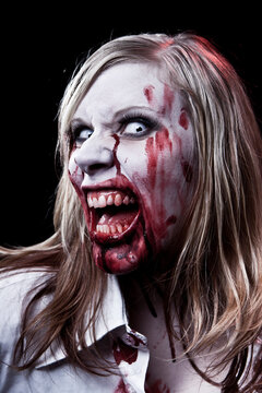 Dark studio photo of a female zombie or vampire with blonde hair on black background.