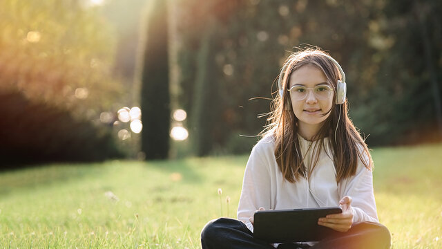 Cute teenager girl is sitting on the park in sunny day and uses tablet pc. Students and education, young people at school