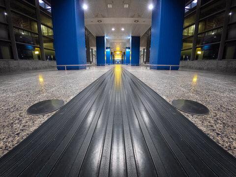 Empty airport corridor interior in perspective. Abstract grey futuristic corridor interior. Corridor rubber carpet for suitcases in perspective.