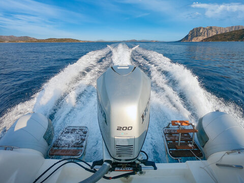 Baunei, Italy 28/07/2020; The stern of a dinghy boat at high speed navigation powered by a Honda 200 hp outboard engine, in the background the Sardinian island of Tavolara.