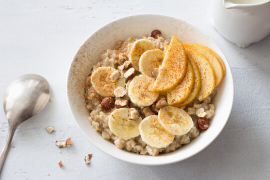 Delicious healthy breakfast. Oatmeal with banana, apple, nuts and cinnamon on a light gray background, top view