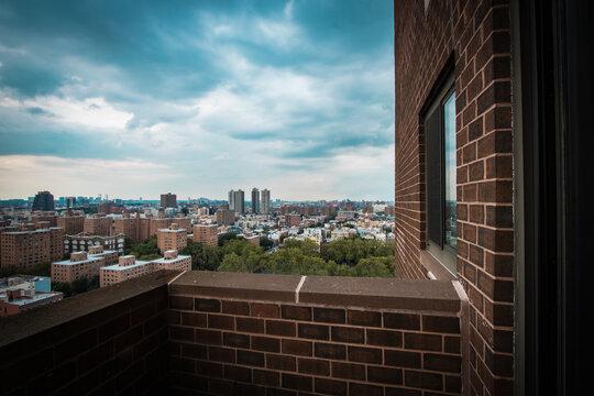 Der Blick auf Harlem aus einem Hochhaus. Dramatischer dunkler Himmel mit düsteren Wolken. Die Aussicht von einem Balkon auf einige Wolkenkratzer, Wohnhäuser und Parks / Parkanlagen.