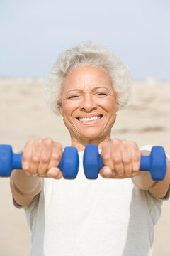 Portrait a cheerful African American senior woman exercising with dumbbells at beach