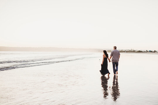 Romantic couple holding hands walking in the surf
