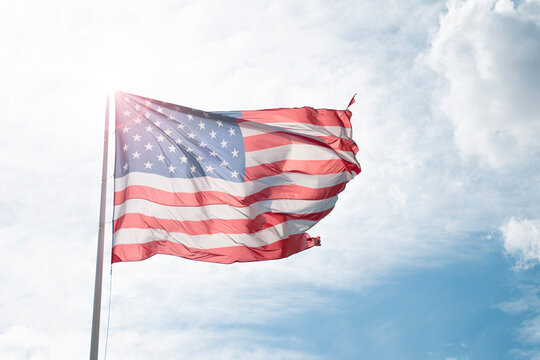 United States od America flag over blue and cloudy sky