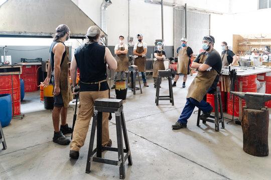 Company of blacksmiths in workshop