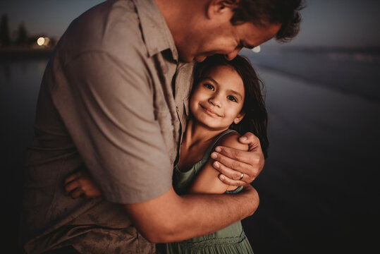 Loving father embracing beautiful 8 yr old daughter with dark eyes