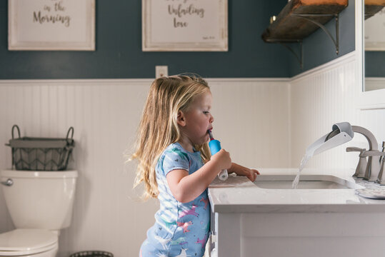 Toddler girl brushing teeth with electric toothbrush for bed