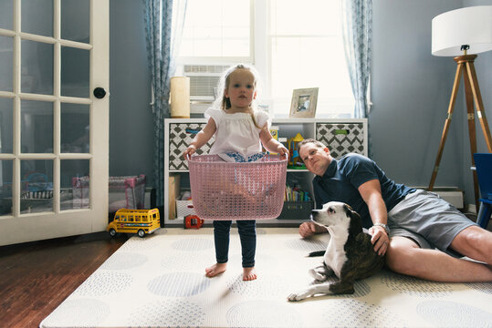 Daughter walking with play basket while dad and pet dog look on