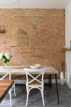 Large exposed brick wall and farm house table in modern kitchen