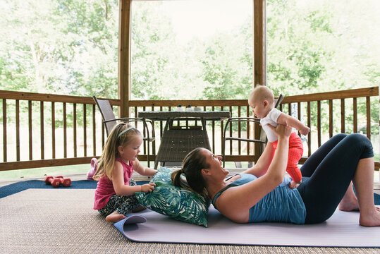 Mother and two young daughters playing and doing fitness together