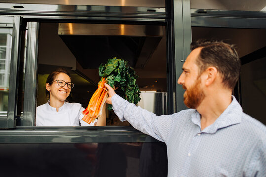 Female chef receiving delivery of vegetables to restaurant