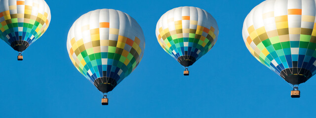 Colorful hot air balloons on blue sky background panorama banner