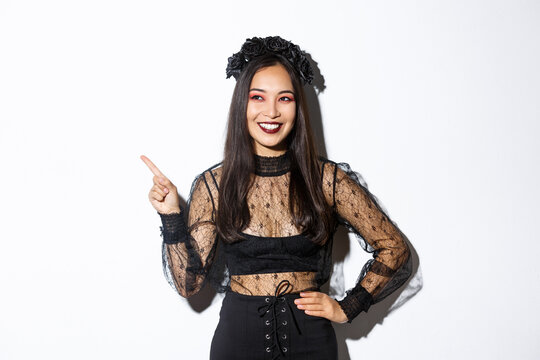Satisfied smiling asian woman in evil witch or banshee costume celebrating halloween, looking pleased and pointing finger upper left corner, showing your promo banner, white background