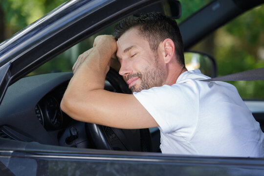 man sleep in car while driving on the road