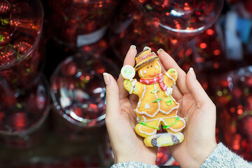 Colorful gingerbread man in female hands