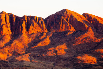 Red coloured cliffs and jagged edges of Mount Sonder early in the morning.