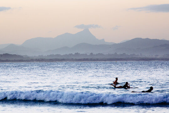 Mount Warning and surfers in the water at Byron Bay on dusk.