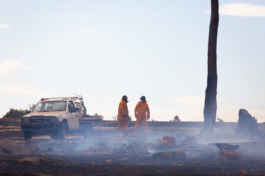 two fire service volunteers with vehicle in burnt out landscape with smoke