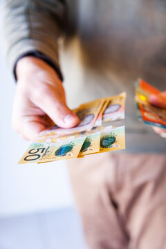 Man holding out fifty and twenty dollar notes australian currency