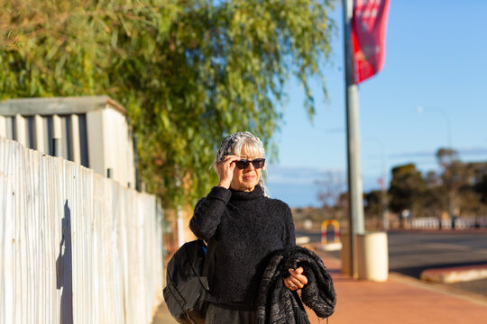Mature aged woman walking down street in outback town