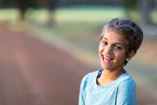 smiling happy child outdoors with blurred background