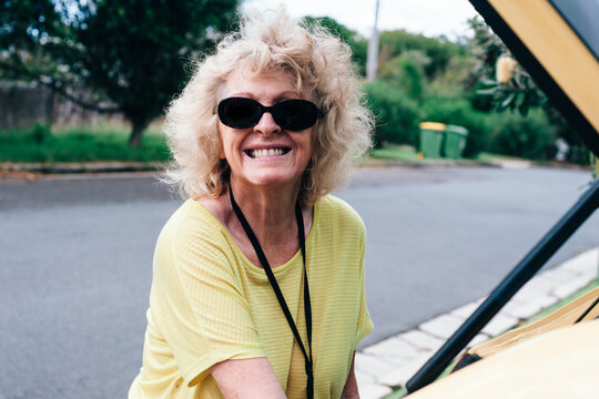 senior woman in yellow t-shirt and sunglasses packing her car in a suburban street