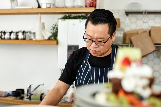 Asian chef working in kitchen at organic food cafe