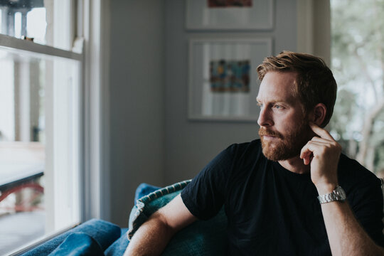 Thoughtful man looking through window while sitting on sofa at home