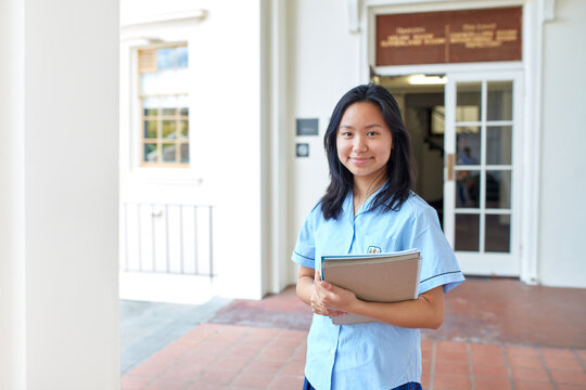 Young Asian student in front of school building holding books