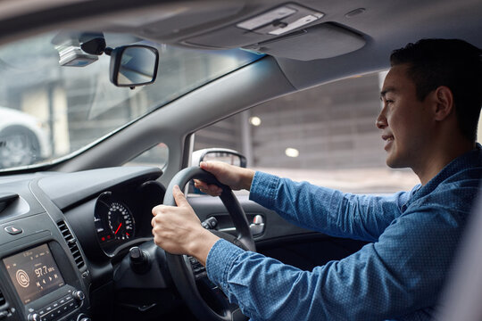 Asian man driving in car