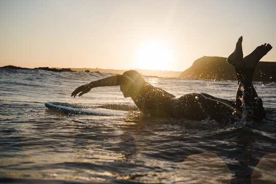 Girl surfing in the ocean on a longboard during sunset