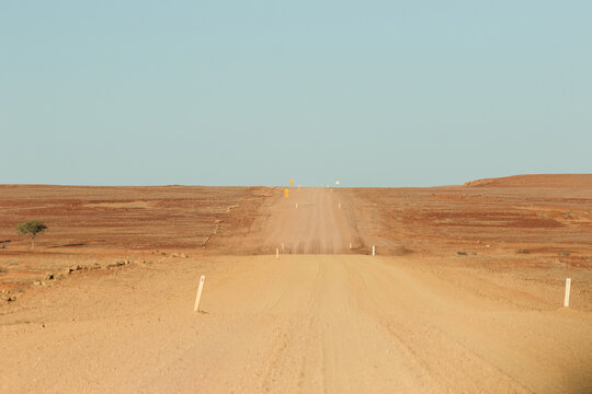 Wide outback dirt road with blue sky